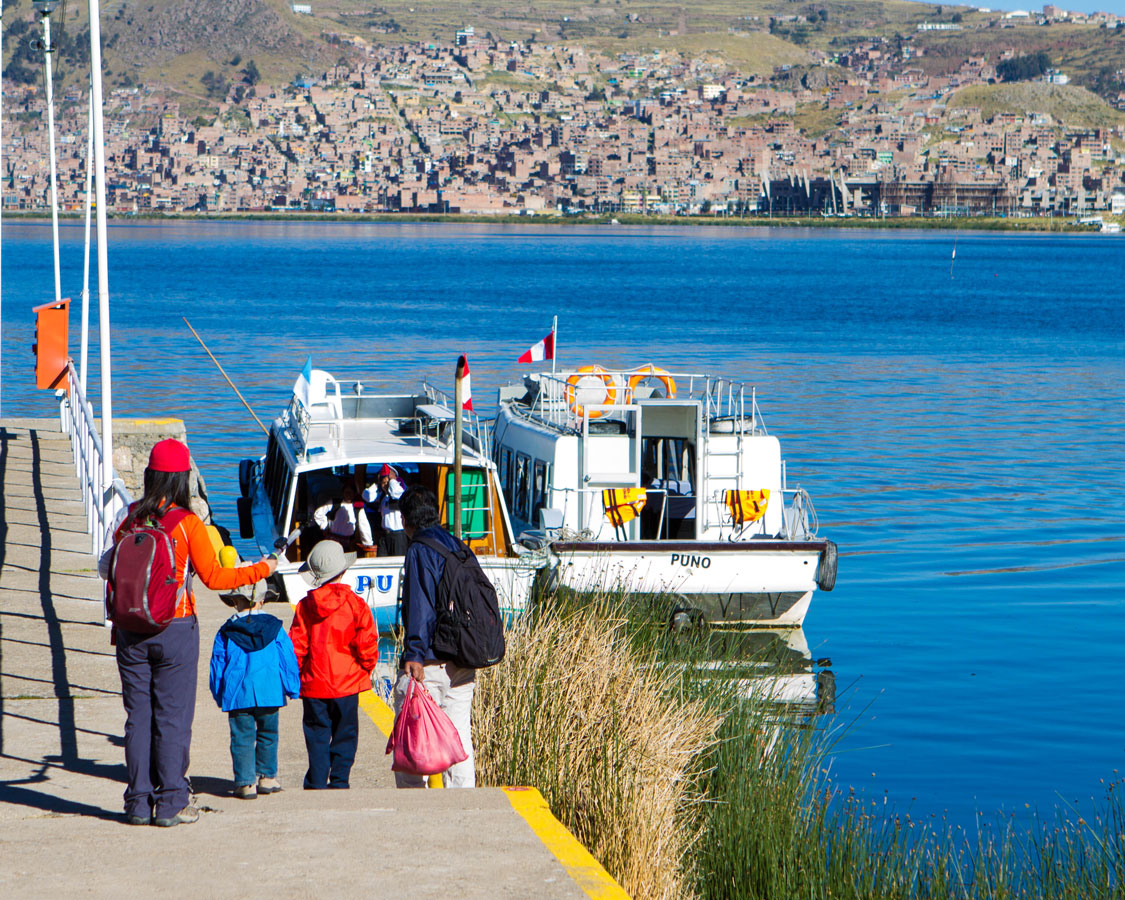 A family boards a tour boat at the Libertador Marina in Puno, Peru as they prepare to visit Lake Titicaca with kids