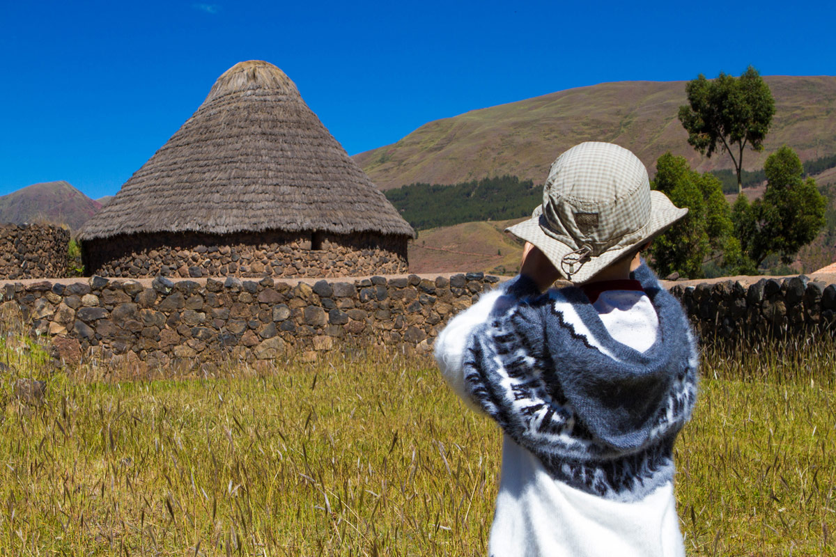 A young boy takes a photograph of inca silos in Raqchi Peru during the Cusco to Puno bus tour in Peru