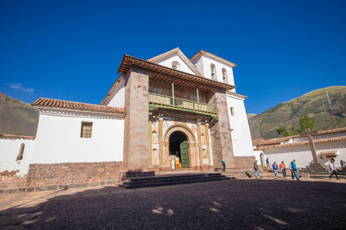 An adobe clad spanish style baroque church with a stone base is lit by the sun in Andahuaylillas Peru