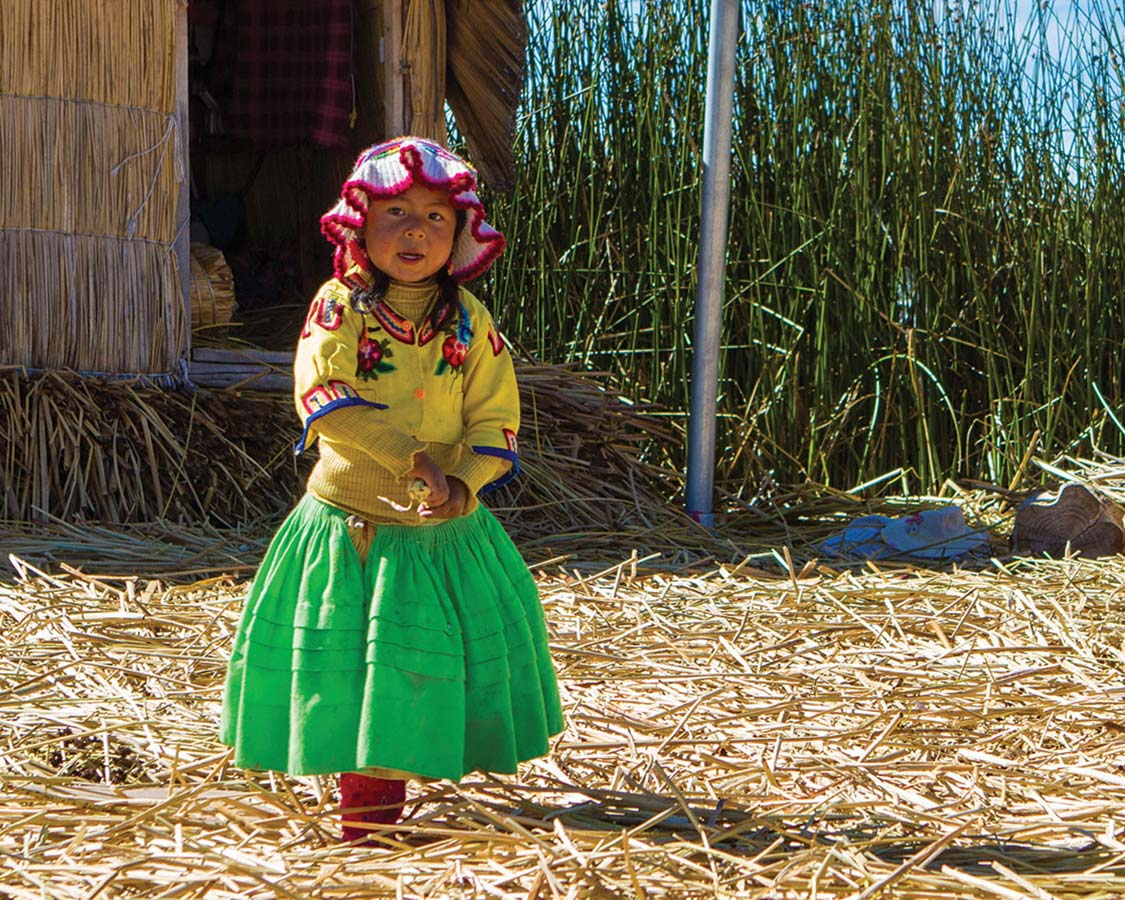 A young Uru girl in traditional clothing walks on a reed island in Isla de los Uros on Lake Titicaca with kids