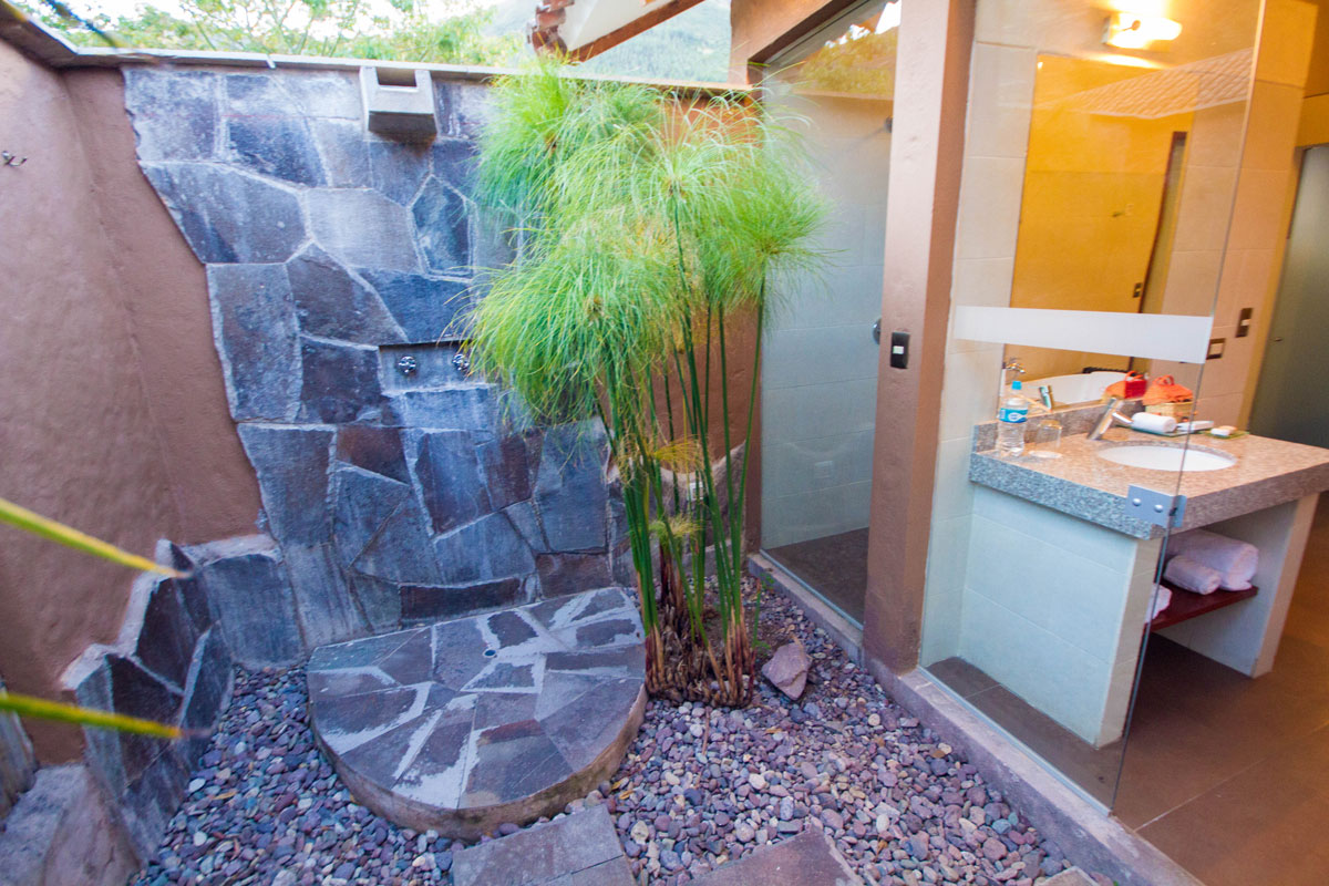 An outdoor shower at the Casa Andina Private Collection Sacred Valley Peru features a stone wall and surrounding plants