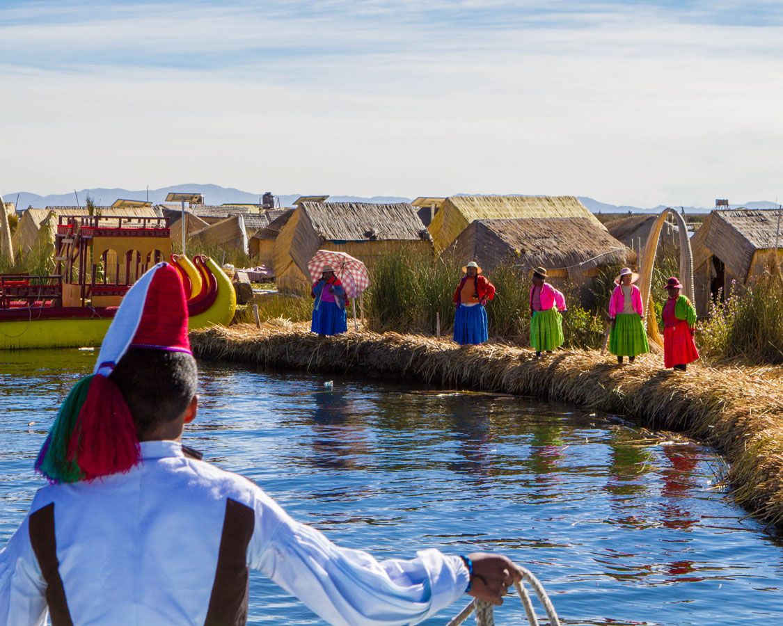 Taquileanos boat operator prepares to dock on Isla de los Uros on Lake Titicaca Peru. What a sight to see while visiting Lake Titicaca with Kids