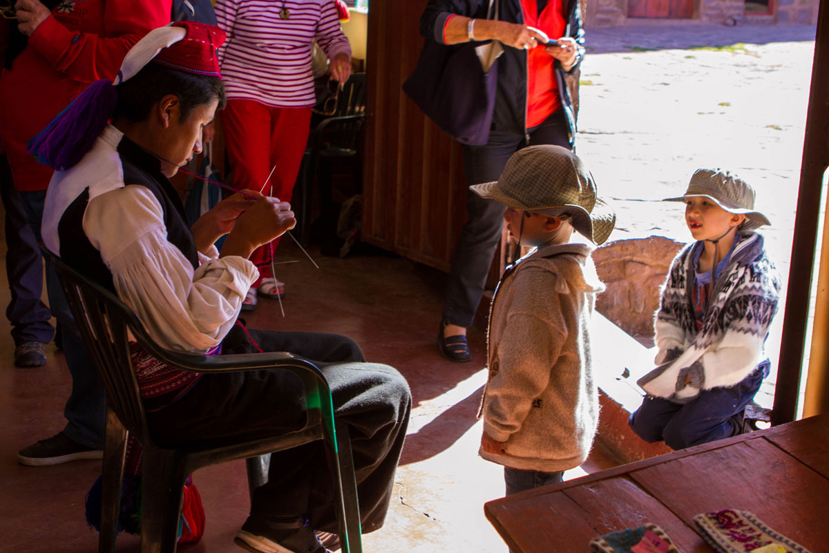 While visiting Lake Titicaca with kids we came across a young Taquileano man in traditional clothing knitting inside the handicraft store on Isla Taquile