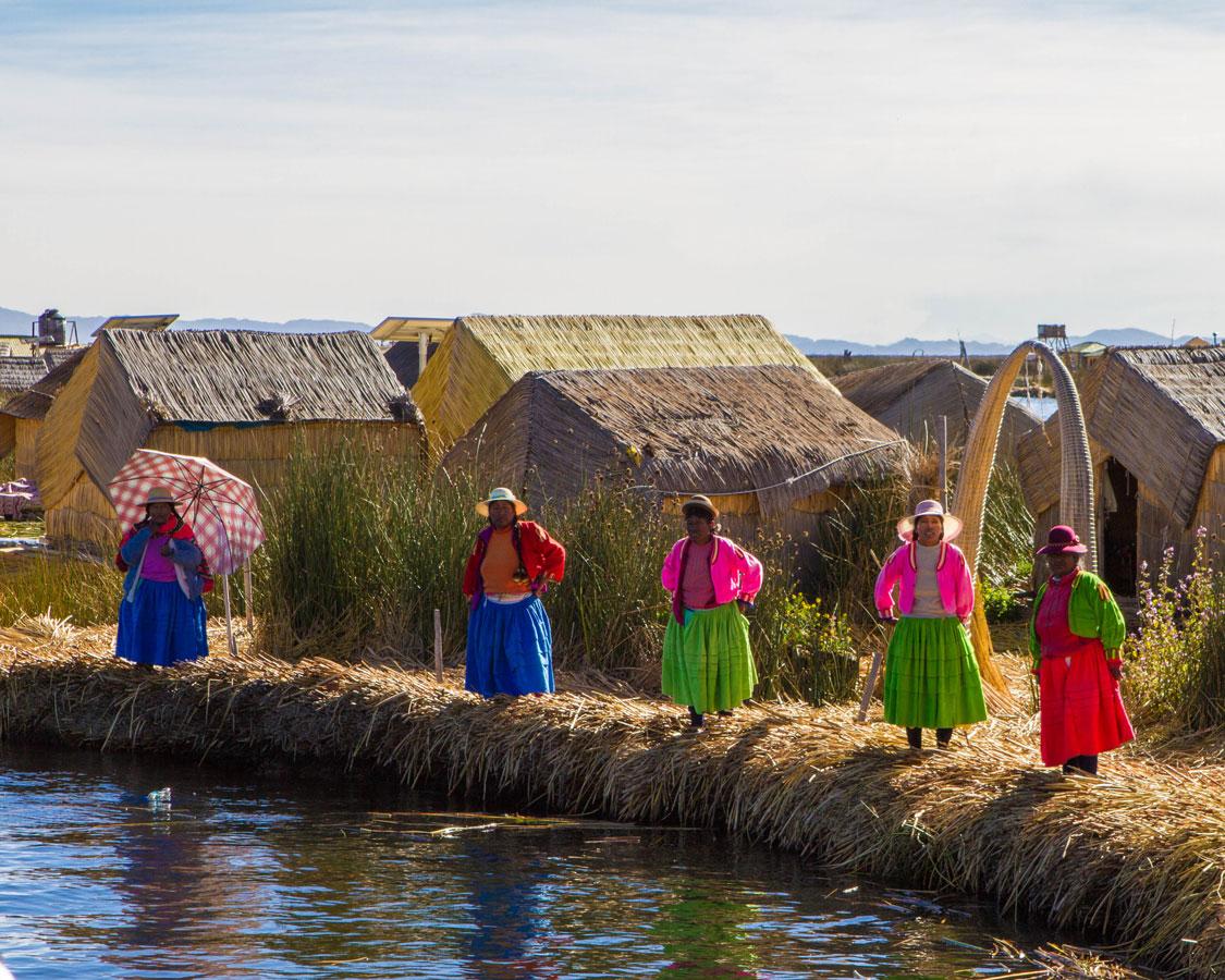 Uros women in traditional clothing prepare to greet visitors to Isla de los Uros on Lake Titicaca Peru