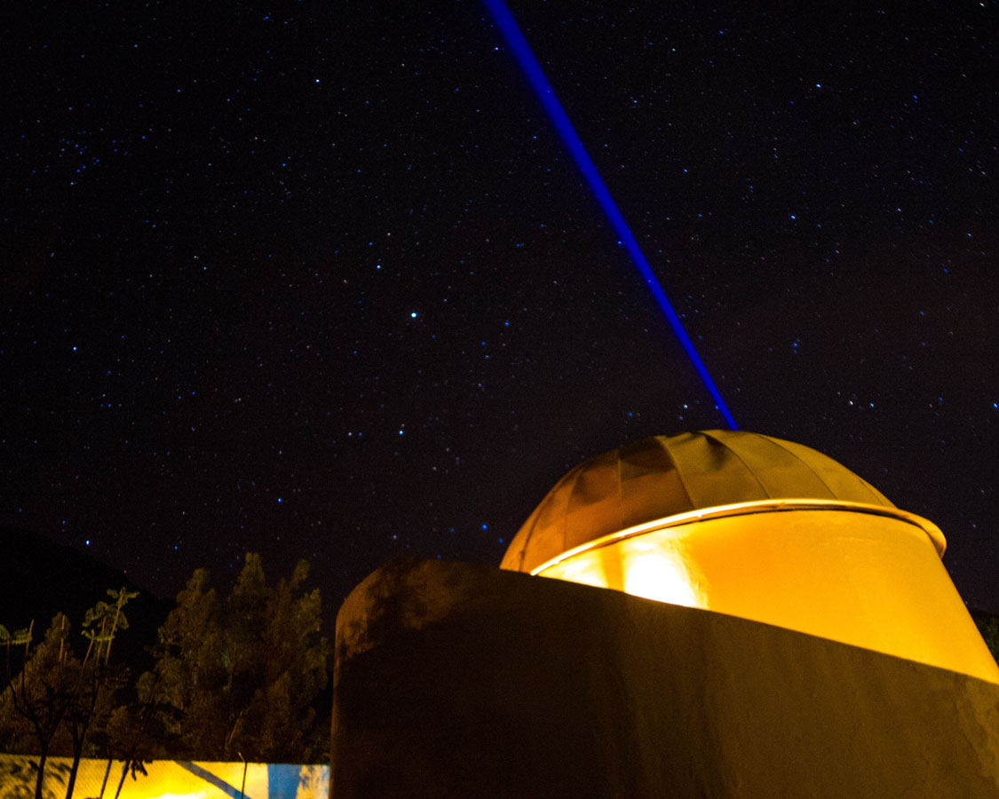 A blue laser shines in the sky of the Planetarium at the Casa Andina Private Collection Sacred Valley Peru