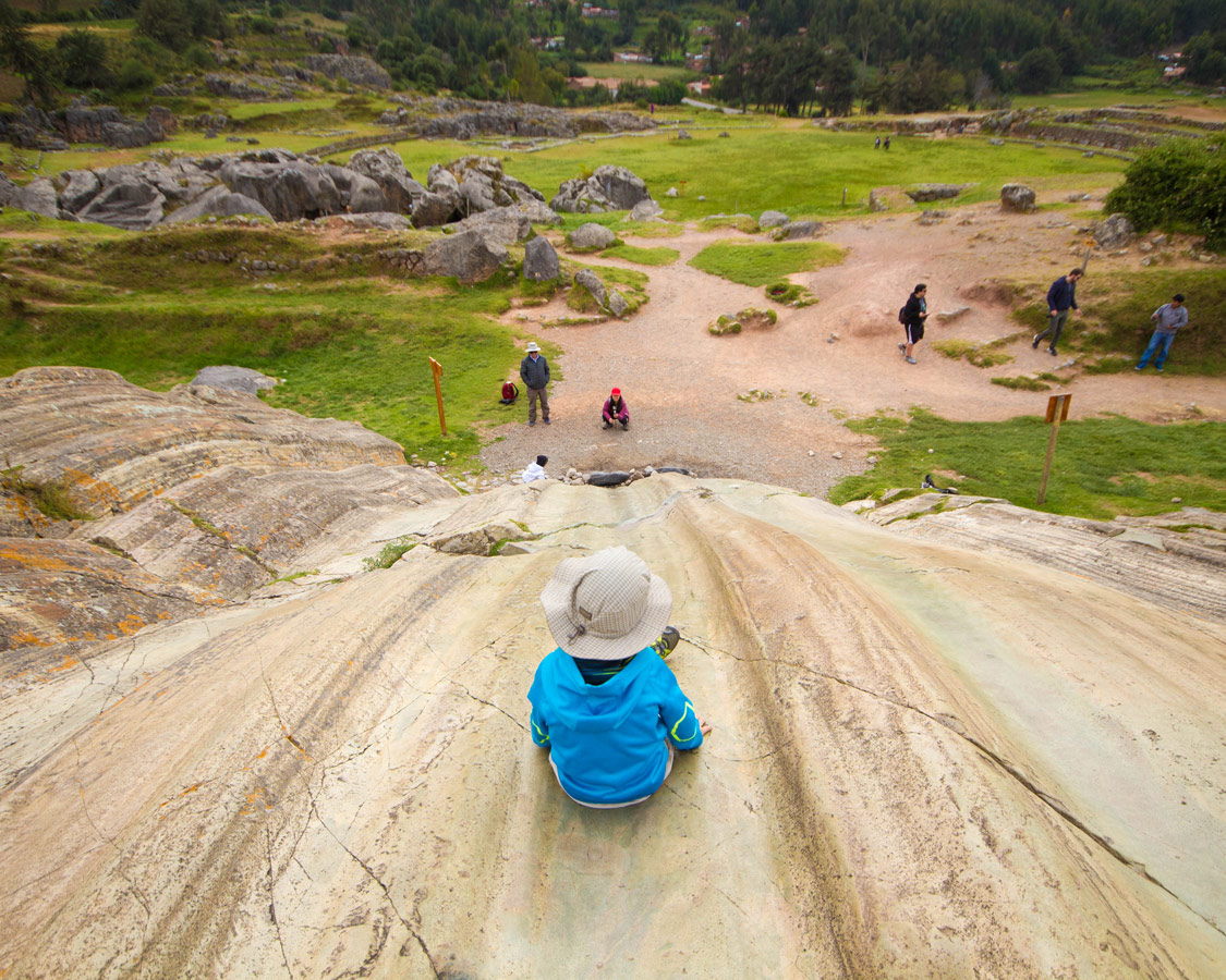 A young boy prepares to slide down the rock slides in Sacsaywaman, one of the best things to see in Cusco Peru