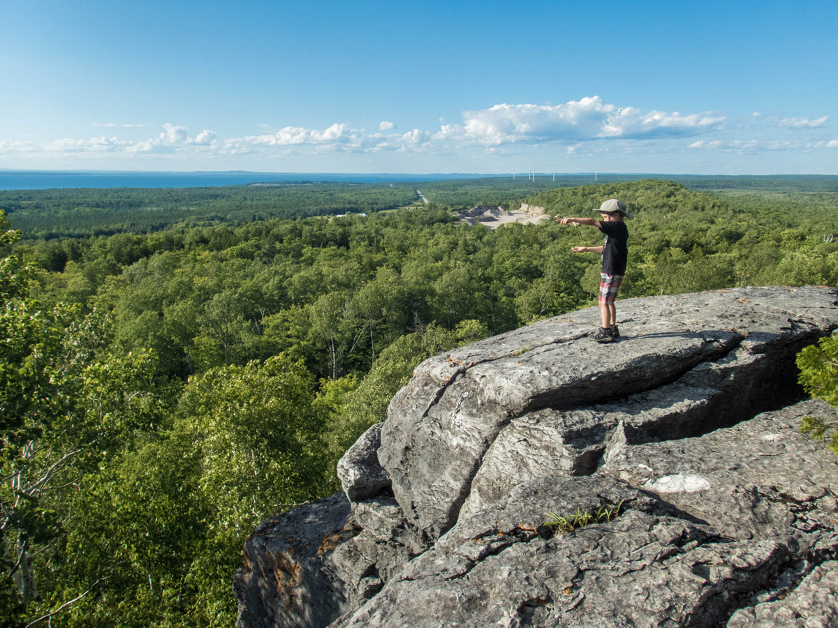 A young boy points into the distance on the top of a rock on the Cup and Saucer Hiking Trail on Manitoulin Island. The Cup and Saucer Trail is one of the top things to do on Manitoulin Island