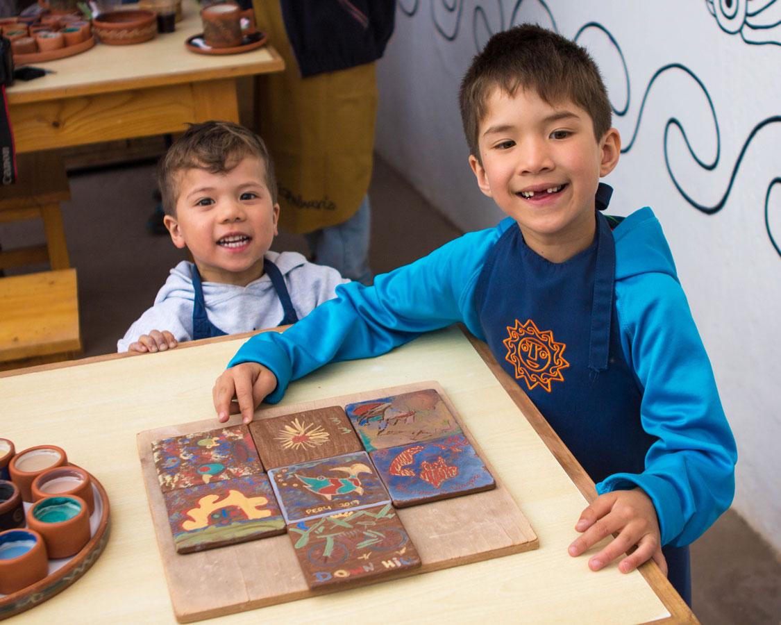 Painting clay tiles at Ceramica Seminario in Urubamba Peru with kids on a 14 day Peru itinerary