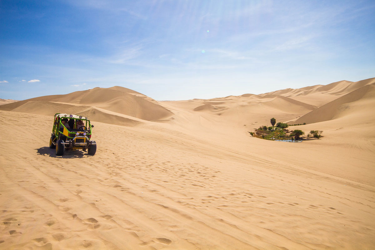 Tearing through the sand dunes of Huacachina Peru in a monster dune buggy while travelling through Peru with kids