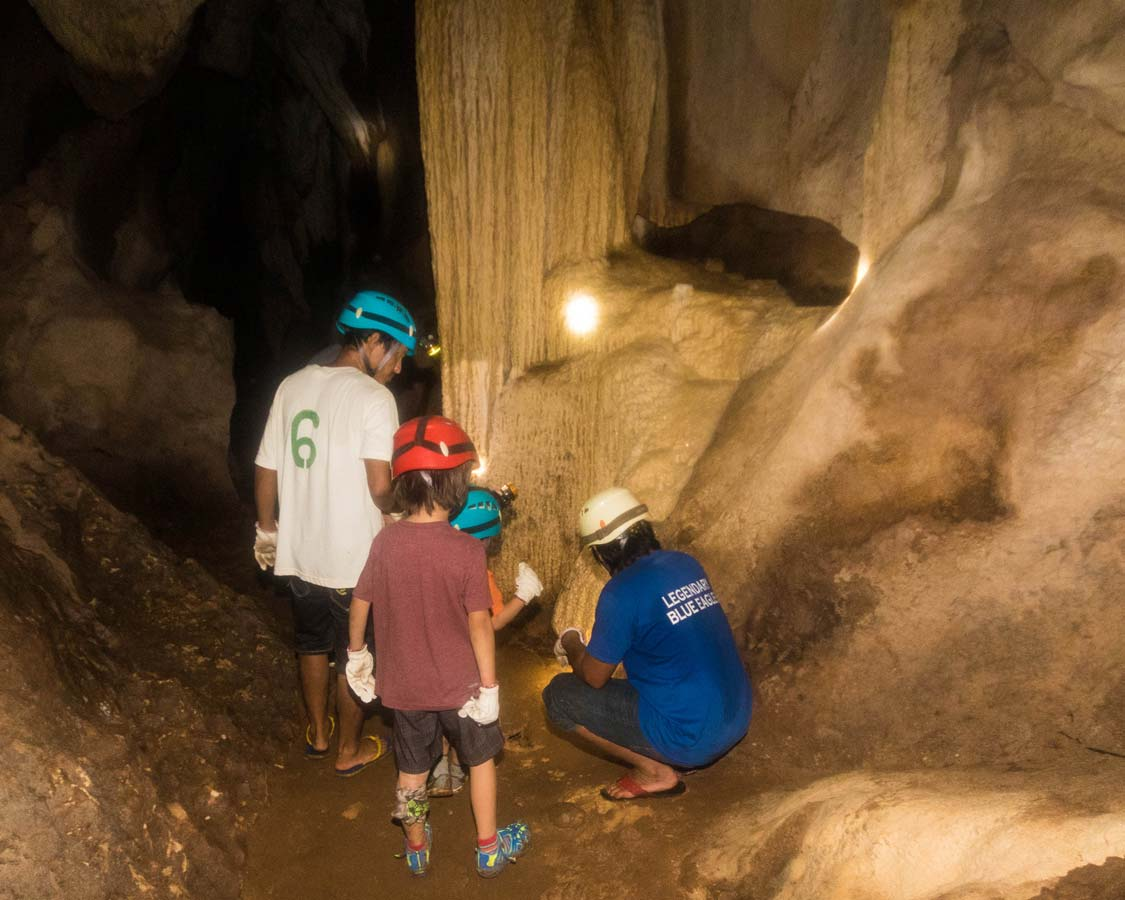 Guides show two boys cave features at Hundred Caves Puerto Princesa Philippines
