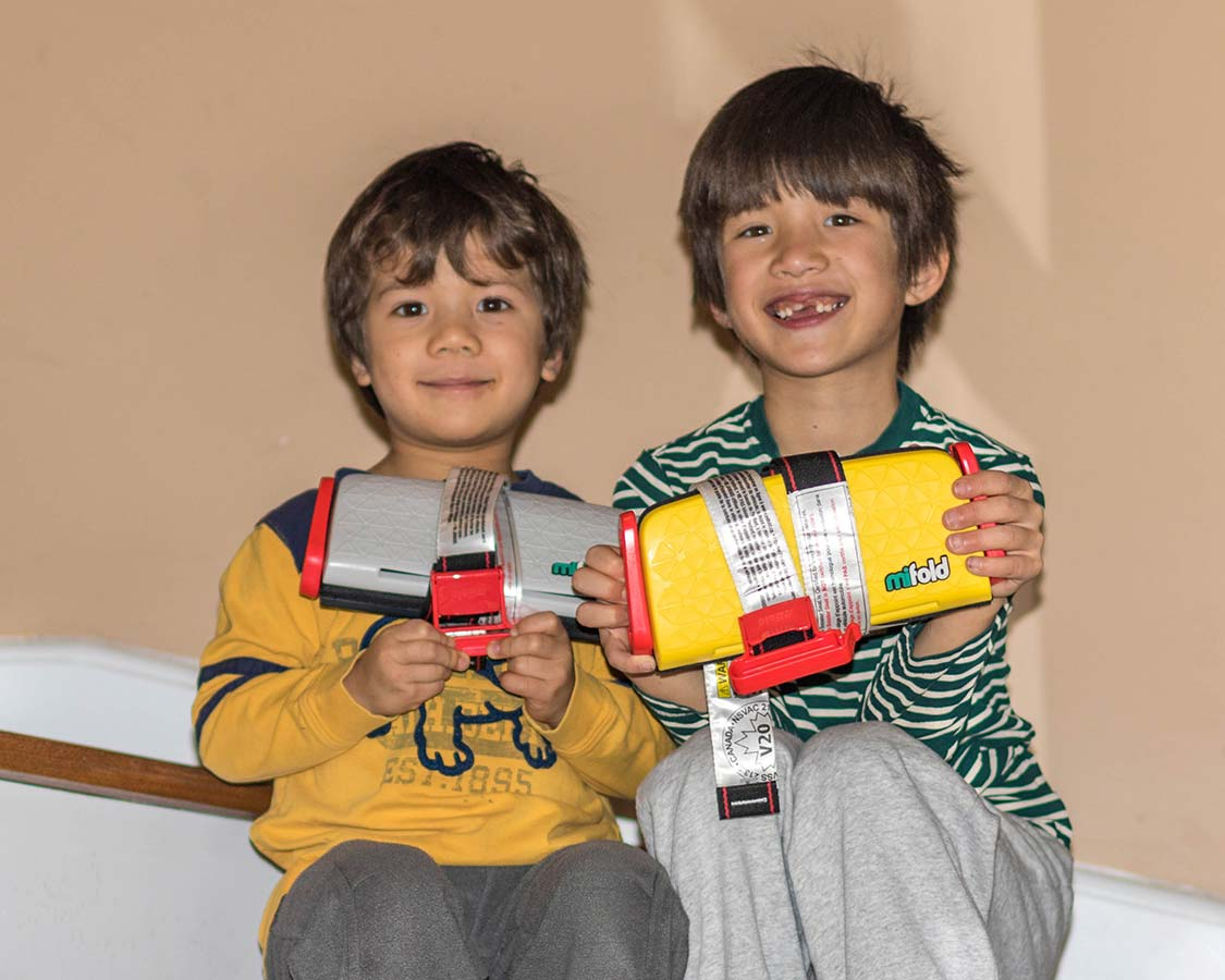 Children holding Mifold booster seats