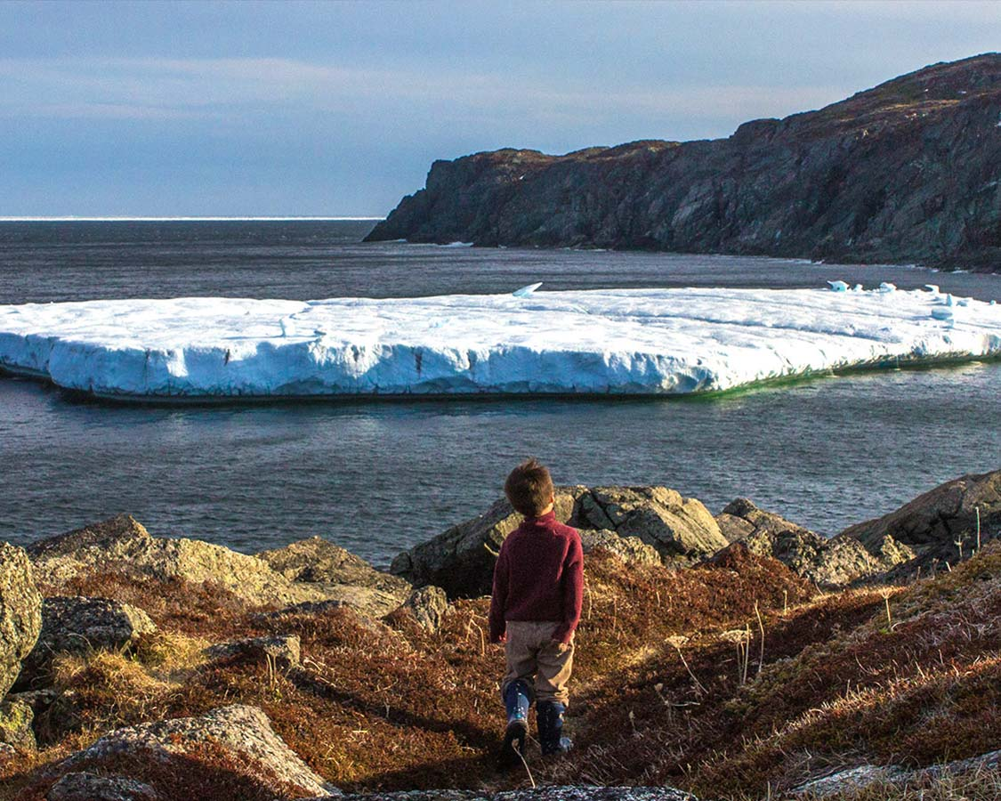 Young boy in red sweater walks along rocky coast towards an iceberg
